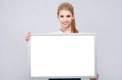Νέο κορίτσι που χαμογελά και που κρατά έναν λευκό κενό πίνακα. Στοκ εικόνα με δικαίωμα ελεύθερης χρήσης
