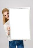 Νέο κορίτσι που χαμογελά και που κρατά έναν λευκό κενό πίνακα. Στοκ Εικόνες