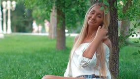 Νέο κορίτσι που χαμογελά στη κάμερα που εγκαθιστά στο πάρκο φιλμ μικρού μήκους