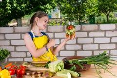Νέο κορίτσι που χαμογελά στο βάζο φρέσκων λαχανικών της Στοκ Φωτογραφία