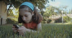 Νέο κορίτσι που χρησιμοποιεί ένα κινητό τηλέφωνο υπαίθρια στη χλόη απόθεμα βίντεο