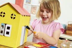 Νέο κορίτσι που χρωματίζει το πρότυπο σπίτι στο εσωτερικό Στοκ εικόνες με δικαίωμα ελεύθερης χρήσης