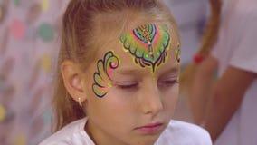 Νέο κορίτσι προσώπου ενώ το πολύχρωμο aquagrim εφαρμογής με ακτινοβολεί στο δέρμα απόθεμα βίντεο