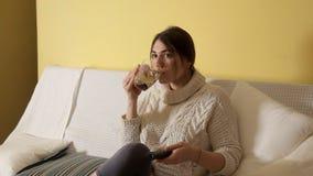 Νέο κορίτσι σε ένα άνετο θερμό πουλόβερ το χειμερινό βράδυ που πίνει το τσάι και που προσέχει στο σπίτι τη TV απόθεμα βίντεο