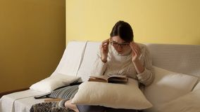 Νέο κορίτσι σε ένα άνετο θερμό πουλόβερ σε ένα χειμερινό βράδυ στο σπίτι, που βάζει στα γυαλιά που διαβάζουν ένα βιβλίο Χειμώνας  απόθεμα βίντεο