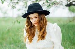 Νέο κορίτσι σε ένα άσπρο φόρεμα και μαύρο καπέλο στο μέσα άσπρο ΛΦ Στοκ φωτογραφία με δικαίωμα ελεύθερης χρήσης