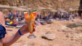 Νέο κορίτσι σε ένα κοστούμι λουσίματος με έναν εξωτικό χυμό διαθέσιμο στην παραλία στην Αίγυπτο απόθεμα βίντεο