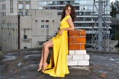 Νέο κορίτσι σε ένα μακρύ κίτρινο φόρεμα στη στέγη ενός κτηρίου στην πόλη Στοκ Φωτογραφία