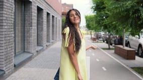 Νέο κορίτσι σε ένα μακρύ φόρεμα μετά από να ψωνίσει με τις τσάντες στα χέρια 4K απόθεμα βίντεο
