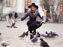 Νέο κορίτσι σε ένα μοντέρνο καπέλο, στο παιχνίδι οδών με έναν μεγάλο αριθμό περιστεριών Μύγα πουλιών επάνω Στοκ φωτογραφία με δικαίωμα ελεύθερης χρήσης