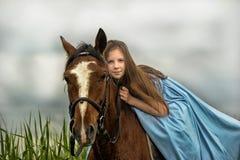 Νέο κορίτσι σε ένα μπλε φόρεμα σε ένα άλογο Στοκ Εικόνες