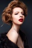 Νέο κορίτσι σε ένα παλτό γουνών και ένα φωτεινό makeup Όμορφο πρότυπο με τα κόκκινα χείλια και hairstyle Στοκ φωτογραφίες με δικαίωμα ελεύθερης χρήσης