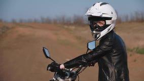 Νέο κορίτσι σε μια μισή στροφή που εξετάζει τη κάμερα καθμένος σε μια μοτοσικλέτα φιλμ μικρού μήκους