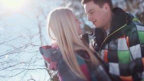Νέο κορίτσι σε μια ρόδινη ένδυση σκι και όμορφος νεαρός άνδρας σε ένα πράσινο κοστούμι χειμερινού αθλητισμού Δεσμευμένοι άνθρωποι απόθεμα βίντεο