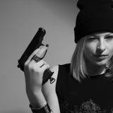 Νέο κορίτσι σε μια σκοτεινή ΚΑΠ με ένα αυξημένο πυροβόλο όπλο. Ξανθός με ένα πυροβόλο όπλο. Στοκ φωτογραφίες με δικαίωμα ελεύθερης χρήσης