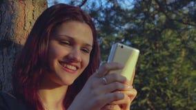 Νέο κορίτσι σπουδαστών που χρησιμοποιεί το smartphone της έξω απόθεμα βίντεο