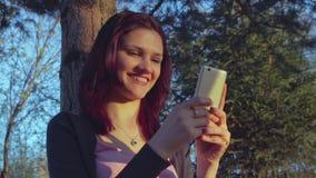 Νέο κορίτσι σπουδαστών που χρησιμοποιεί το smartphone της σε ένα πάρκο απόθεμα βίντεο