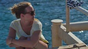 Νέο κορίτσι στα γυαλιά ηλίου που κάθεται κοντά στην ακτή μια ηλιόλουστη ημέρα απόθεμα βίντεο