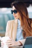 Νέο κορίτσι στα γυαλιά ηλίου που πίνουν τον καφέ στην οδό και που διαβάζουν τις ειδήσεις σε μια ταμπλέτα Στοκ εικόνες με δικαίωμα ελεύθερης χρήσης