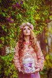 Νέο κορίτσι στα ιώδη λουλούδια Στοκ Εικόνες