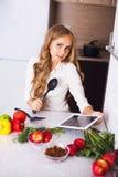 Νέο κορίτσι στην κουζίνα που ψάχνει μια συνταγή στην ταμπλέτα Στοκ Εικόνα