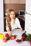 Νέο κορίτσι στην κουζίνα που ψάχνει μια συνταγή στην ταμπλέτα Στοκ Φωτογραφία