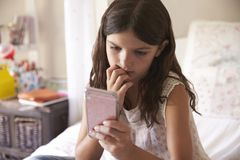 Νέο κορίτσι στην κρεβατοκάμαρα που ανησυχείται από το μήνυμα κειμένου φοβέρας Στοκ Εικόνες