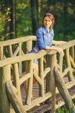 Νέο κορίτσι στην ξύλινη γέφυρα Στοκ Εικόνες