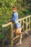 Νέο κορίτσι στην ξύλινη γέφυρα Στοκ Φωτογραφία