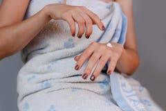 Νέο κορίτσι στην πετσέτα που βάζει την κρέμα σε ετοιμότητα Στοκ Εικόνα