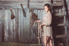 Νέο κορίτσι στη σιταποθήκη με ένα σχοινί στα χέρια της στοκ εικόνες