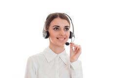Νέο κορίτσι στις άσπρες στάσεις πουκάμισων στα ακουστικά με το μικρόφωνο, χαμόγελο Στοκ Εικόνα