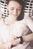 Νέο κορίτσι στον καναπέ με το smartwatch Στοκ φωτογραφία με δικαίωμα ελεύθερης χρήσης