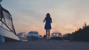 Νέο κορίτσι στον μπλε περίπατο φορεμάτων στην ξύλινη αποβάθρα στην ακτή στο ηλιοβασίλεμα άσπρα γιοτ απόθεμα βίντεο