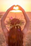 Νέο κορίτσι στον τομέα σίτου που κάνει το σύμβολο καρδιών στο ηλιοβασίλεμα Στοκ εικόνες με δικαίωμα ελεύθερης χρήσης