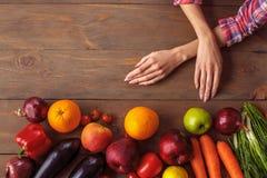 Νέο κορίτσι στον υγιή τρόπο ζωής κουζινών που κλίνει στον πίνακα με την κινηματογράφηση σε πρώτο πλάνο φρούτων και λαχανικών στοκ εικόνα