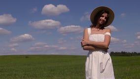 Νέο κορίτσι στο άσπρο καπέλο φορεμάτων και αχύρου απόθεμα βίντεο