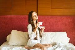 Νέο κορίτσι στο άσπρο τσάι κατανάλωσης τηβέννων στο κρεβάτι στοκ εικόνες