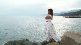 Νέο κορίτσι στο άσπρο φόρεμα που στέκεται στο βράχο θαλασσίως απόθεμα βίντεο