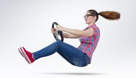 Νέο κορίτσι στο αυτοκίνητο οδηγών γυαλιών με μια ρόδα Στοκ Φωτογραφίες