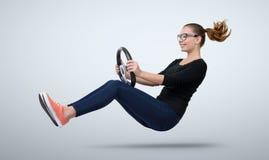 Νέο κορίτσι στο αυτοκίνητο οδηγών γυαλιών με μια ρόδα Στοκ Εικόνες