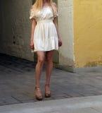 Νέο κορίτσι στο θερινό φόρεμα στα ελαφριά πάνινα παπούτσια στην τοποθέτηση οδών Στοκ Εικόνα