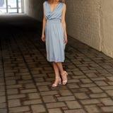 Νέο κορίτσι στο θερινό φόρεμα στα ελαφριά πάνινα παπούτσια στην τοποθέτηση οδών Στοκ Φωτογραφίες