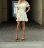 Νέο κορίτσι στο θερινό φόρεμα στα ελαφριά πάνινα παπούτσια στην τοποθέτηση οδών Στοκ Φωτογραφία