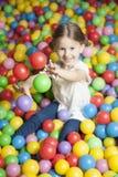 Νέο κορίτσι στο κοίλωμα σφαιρών που ρίχνει τις χρωματισμένες σφαίρες Στοκ φωτογραφίες με δικαίωμα ελεύθερης χρήσης