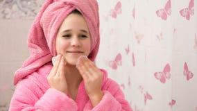 Νέο κορίτσι στο λουτρό που καθαρίζει το πρόσωπό του με τα μαξιλάρια βαμβακιού απόθεμα βίντεο