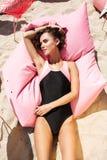 Νέο κορίτσι στο μαγιό που βρίσκεται και που κάνει ηλιοθεραπεία στο μεγάλο ρόδινο μαξιλάρι στην παραλία Πορτρέτο του όμορφου κοριτ στοκ φωτογραφία