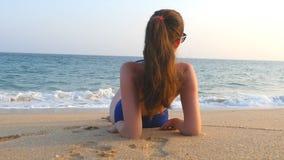Νέο κορίτσι στο μαγιό που βρίσκεται στην παραλία και την ηλιοθεραπεία θάλασσας Όμορφη καυκάσια χαλάρωση γυναικών στην ωκεάνια ακτ απόθεμα βίντεο