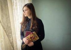 Νέο κορίτσι στο μαύρο εκλεκτής ποιότητας φόρεμα Στοκ Εικόνες