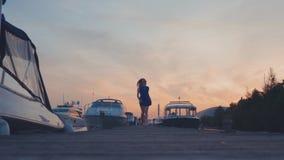 Νέο κορίτσι στο μπλε φόρεμα που οργανώνεται στην ξύλινη αποβάθρα στην ακτή στο ηλιοβασίλεμα άσπρα γιοτ απόθεμα βίντεο